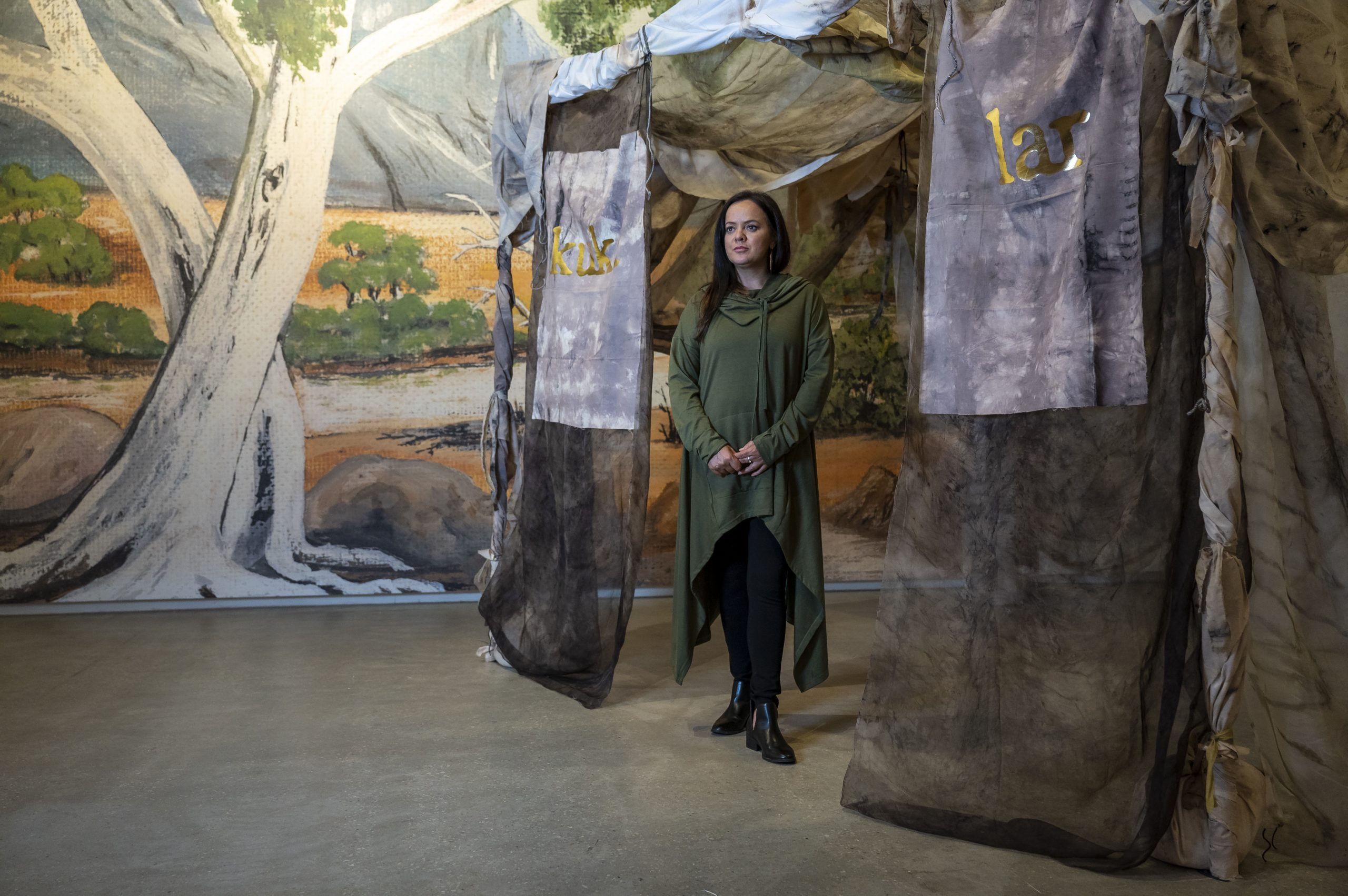 Stacie Piper stands at the entrance of Paola Balla's artwork